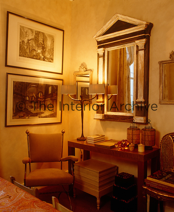 Two framed prints and ornate mirrors are grouped together in a corner of the dining room