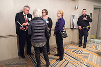 "Sara Altherr, of Kingston, Mass., (center, turned away from camera) speaks with Nuclear Regulatory Commission officials (from left) Ray Lorson, Director of NRC Region 1 Division of Reactor Safety, Erin Carfang, Senior Resident Inspector at Pilgrim, and Lindsay Brandt, Acting Resident Inspector at Pilgrim, after a public hearing regarding Pilgrim Station, a nuclear power plant run by Entergy, at Hotel 1620 in Plymouth, Massachusetts, USA, on Tues., Jan. 31, 2017. Altherr raised concerns about the vulnerability of the plant to attack, including from airplanes from regional airports. An email from the NRC was leaked in December 2016 outlining problems with the ""safety culture"" at the plant and an ""overwhelmed"" staff. Area residents have been calling for the plant to be shut down. The green signs in the audience, reading ""Shut Pilgrim Now,"" are from a group of area residents calling for the plant's closure called Cape Downwinders."