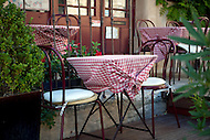 Cafe tables are set & ready for lunch customers at a cafe in Gordes, France