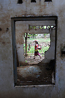 An Indonesian woman walks past an abandoned building in central Jakarta.<br /> <br /> To license this image, please contact the National Geographic Creative Collection:<br /> <br /> Image ID: 1588059 <br />  <br /> Email: natgeocreative@ngs.org<br /> <br /> Telephone: 202 857 7537 / Toll Free 800 434 2244<br /> <br /> National Geographic Creative<br /> 1145 17th St NW, Washington DC 20036