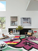 An inspiring, open plan living space with a double height ceiling. A white Eames recliner and ottoman and a Nordic retro armchair stand on a vibrant carpet by Carpet Diem.
