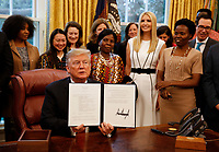 "United States President Donald J. Trump shows off the document after signing the National Security Presidential Memorandum to Launch the ""Women's Global Development and Prosperity"" Initiative in the Oval Office of the White House in Washington, DC on Thursday, February 7, 2019. First Daughter and Advisor to the President Ivanka Trump is pictured in the white dress.<br /> Credit: Martin H. Simon / CNP/AdMedia"