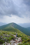 Two hikers descending the Bondcliff Trail in the Pemigewasset Wilderness of the New Hampshire White Mountains during the summer months. The summit of Bondcliff is in the distance and storm clouds fill the sky.