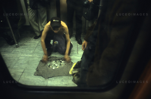 A beggar prepares to press himself against broken glass in a Mexico City subway.  He is paid to stop.