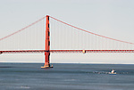 A boat passes beneath the Golden Gate Bridge in San Francisco Bay.