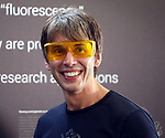Pic shows: Scientist looking at the 'glow in the dark' coral at the Royal Society Summer Exhibition.<br /> <br /> Scientist pop star Brian Cox dons funky yellow shades as visits the glowing coral. Helps them stand out<br /> <br /> <br /> <br /> <br /> Pic by Gavin Rodgers/Pixel 8000 Ltd