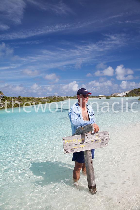 EXUMA, Bahamas. Yves, holding up a sign on Compass Cay.