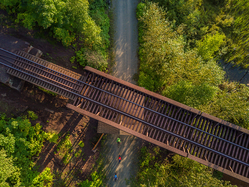 Aerial view of a family biking along the Iron Ore Heritage Trail near Marquette, Michigan. The IOHT follows a former railroad corridor that linked the iron mining commuties of Marquette County with the Lake Superior shipping port in the city of Marquette.