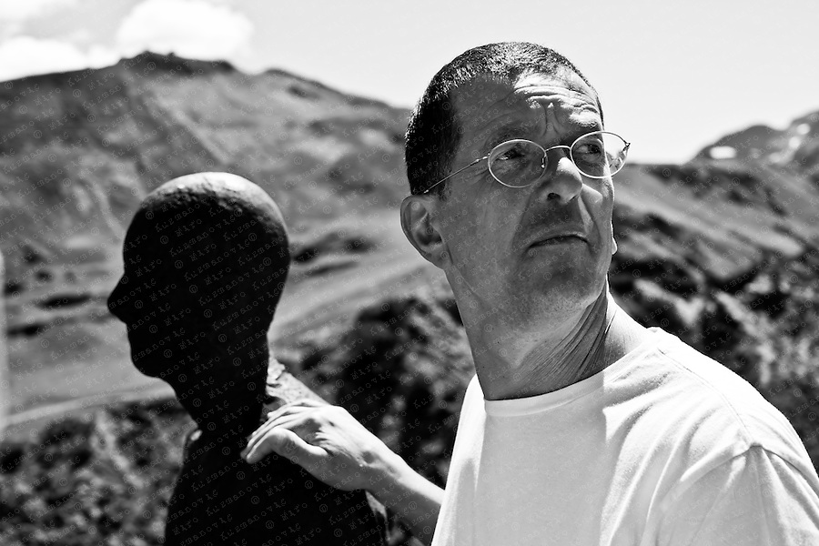"British artist Antony Gormley stands beside one of his ""Horizon Field"" sculptures during his exhibition opening in Lech July 31, 2010. The landscape installation made for the Kunsthaus Bregenz consists of 100 life-size, solid cast iron figures of the human body spread over an area of 150 square kilometres in the Alps forming a horizontal line at 2,039 meters above sea level."