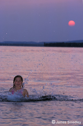 Young girl swimming in the lake at sunset