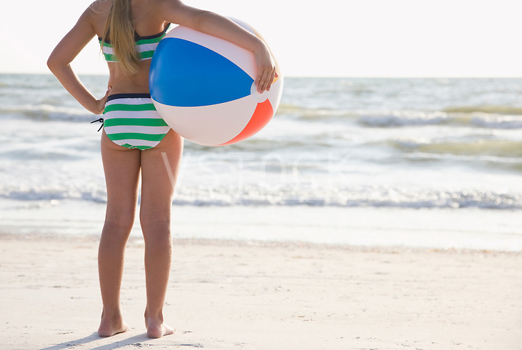 USA, Florida, St. Pete Beach, girl (8-9) standing with ball on beach