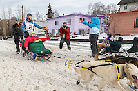 Larry Daugherty runs down Cordova Street giving high-fives during the Ceremonial Start of the 2016 Iditarod in Anchorage, Alaska.  March 05, 2016