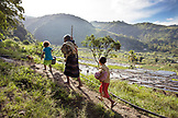 INDONESIA, Flores, a grandfather walks with his grandkids and dog in Waturaka Village