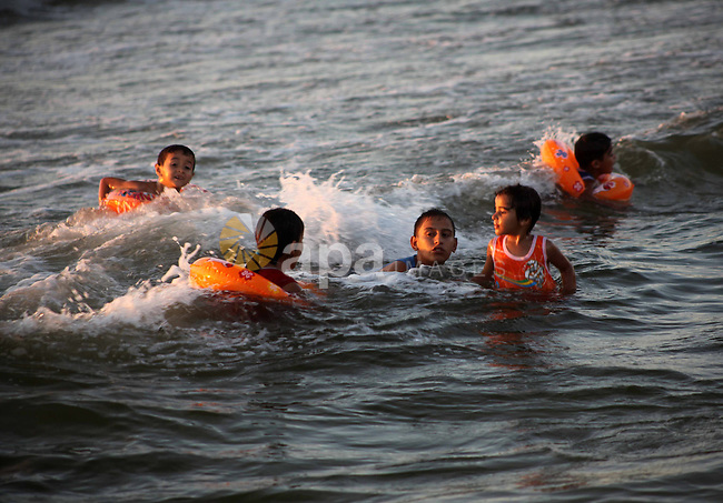 Palestinian children enjoy swimming in the sea at Gaza beach during Friday holiday in Gaza city, Aug 24, 2012. Gazans escape to the beach and out from their homes during heat wave and power outages. Photo by Ashraf Amra