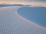 Sunset light illuminates the waves of sand in the gypsum dunes of White Sands National Monument, New Mexico