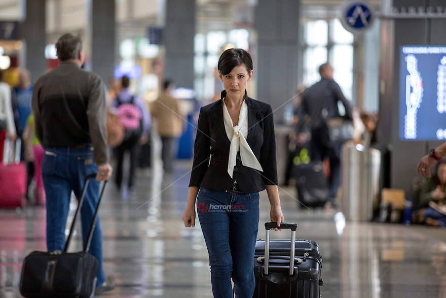 Pretty young female businesswoman passenger carries luggage through the terminal at the Austin–Bergstrom International Airport (ABIA).
