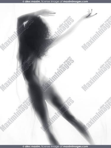 Beautiful surreal silhouette of a nude woman figure rear view in glowing foggy light dancing or falling behing white veil of a sheer curtain fabric