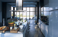 The white lacquered kitchen/dining area leads in to the open-plan living room and the wall of glass doors beyond