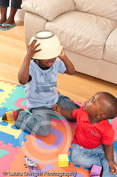 12 month old baby boy sitting on floor looking at his three year old brother who is hiding with a bowl on his head vertical