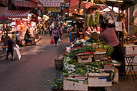 A market street in Hong Kong, with a vegetable stall in the foreground, as evening sets in.