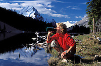 CANADA, ALBERTA, KANANASKIS, MAY 2002. A camper drink from her water bottle at Elbow Lake.  The Kananaskis Country provincial park is home to Canada's most beautiful nature and wildlife. It has also escaped the mass tourism as in Banff National Park. Photo by Frits Meyst/Adventure4ever.com