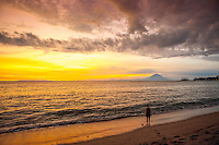 A lone person on the beach looking toward Bali and Gunung Agung, Bali's sacred mountain.