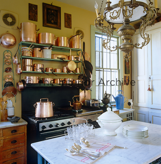 Copper pots and pans of all sizes are stored on metal shelves above the range in this eclectic kitchen