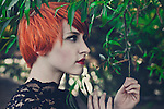 Profile portrait of a young woman looking away, with pale skin, orange hair and red lips, wearing a lace dress, playing with the leaves of a willow, with outdoors background.