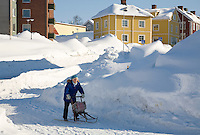 Sweden, SWE, Kiruna, 2008Mar22: An elderly woman riding through the snow in the city centre.