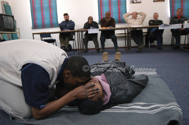First aid instructor James Manamela demonstrates CPR, with the help of female mine worker Sophia Mboni, to other underground employees at Mponeng, an AngloGold Ashanti gold mine in Carltonville.  All underground workers are required to undergo ongoing safety training.
