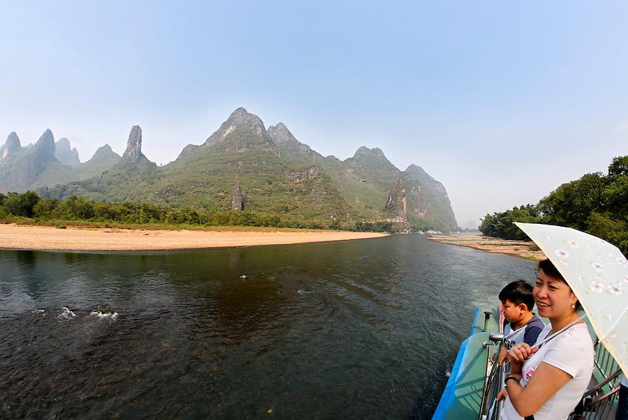 Woman and boy cruising the Lijiang River, Guanxi, China