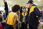 January 25, 2014. Winston Salem, North Carolina.<br /> Kayla Montgomery, 2nd from right, braids her hair and talks to her coach Patrick Cromwell before running in the 1600m at the 2014 David Oliver Classic. The braid is part of her racing routine, and is done the same for every outing.<br />  3 and a half years ago, during an examination after sustaining tailbone and head injuries from a fall during a soccer game, Kayla Montgomery, now 18, was diagnosed with multiple sclerosis. Montgomery, then a decent runner, refused to be limited by her diagnosis, and after years of training has become one of the best high school runners in the country.