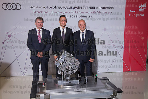 Achim Heinfling (L) president of board of directors Audi Hungaria Zrt, Hungary's minister of foreign affairs and trade Peter Szijjarto (C) and Peter Kossler (R) production and logistics director of Audi AG pose with the first E-Engine at the production start at the Audi factory in Gyor (about 120 km West of Budapest), Hungary on July 24, 2018. ATTILA VOLGYI