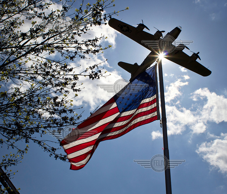 A model of a B-29 Superfortress bomber tops the stars and stripes on a flagpole in Lansing, Iowa.