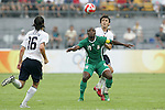 13 August 2008: Promise Isaac (NGA) (10) is defended by Michael Parkhurst (USA) (behind).  The men's Olympic team of Nigeria defeated the men's Olympic soccer team of the United States 2-1 at Beijing Workers' Stadium in Beijing, China in a Group B round-robin match in the Men's Olympic Football competition.