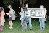 """An NBC reporter interviews Jason Sherfey as he holds a home-made $1000 bill featuring a portrait entrepreneur and Democratic presidential candidate Andrew Yang after the candidate spoke to a large crowd in Cambridge Common near Harvard Square in Cambridge, Massachusetts, on Mon., September 16, 2019. Yang's unlikely presidential bid is centered on his idea for a """"Freedom dividend,"""" which would give USD$1000 per month to every adult in the United States. After appearing in three Democratic party debates, Yang has risen in polls from longshot candidate to within the top 10. Sherfey said that the Los Angeles Yang Gang produced the Yangbucks and he just blew up the design."""
