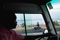 Senegal. Dakar. Early morning, a bus driver rides his coach on the Corniche road along the Atlantic ocean. A man on his scooter passes by while a group of young men train physica, work outl and make sport on the sandy beach. 04.12.09  © 2009 Didier Ruef