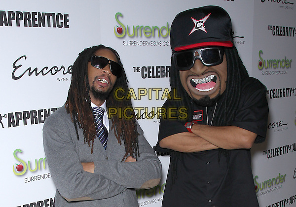 "LIL JON (Jonathan Mortimer Smith) & GUEST.Stars of ""The Celebrity Apprentice"" host cast party at Surrender Nightclub at Encore Las Vegas, Las Vegas, Nevada, USA..March 5th, 2011.half length grey gray cardigan sunglasses shades goatee facial hair teeth bling arms crossed giant oversized mascot head baseball cap hat funny .CAP/ADM/MJT.© MJT/AdMedia/Capital Pictures."
