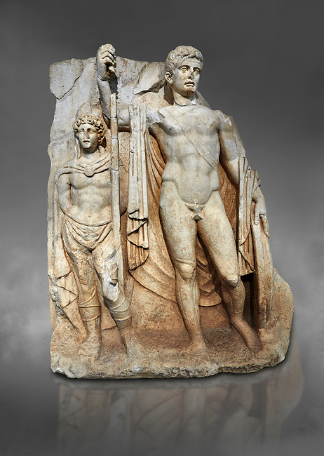 Roman Sebasteion relief  sculpture of emperor Tiberius with a captive Aphrodisias Museum, Aphrodisias, Turkey.  Against a grey background.<br /> <br /> The naked emperor Tiberius stands frontally holding a spear and shield wearing a cloak and a sword strap. Besides him stands a barbarian
