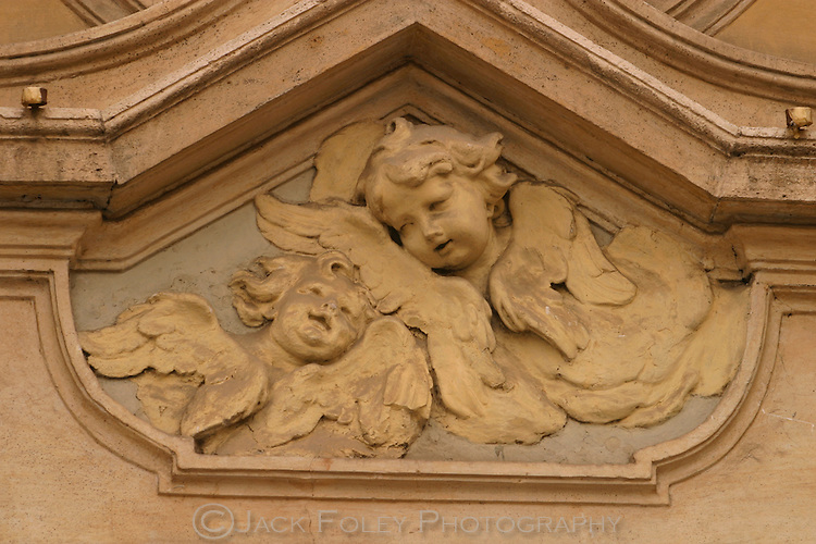 Sculpture of two angels above a doorway in Rome Italy.