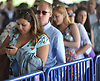Maria Massimo of Hauppauge, left, checks her messages as she waits on line to enter Belmont Park from its connecting LIRR train station during the 150th running of the Belmont Stakes on Saturday, June 9, 2018