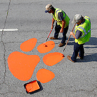 Don Johnson, left, and Michael Porter, both with the City of Clemson Streets Department, put a fresh coat of orange paint on a tiger paw on S.C. 93 on campus on Tuesday. Workers said that they would repaint about 150 paws around the city in the coming week to prepare for the new school year.