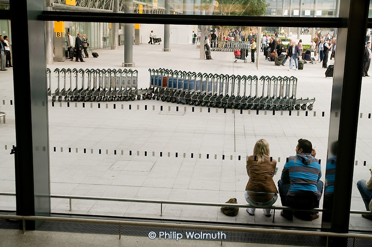 Waiting passengers and baggage trolleys at Terminal 3 of Heathrow Airport