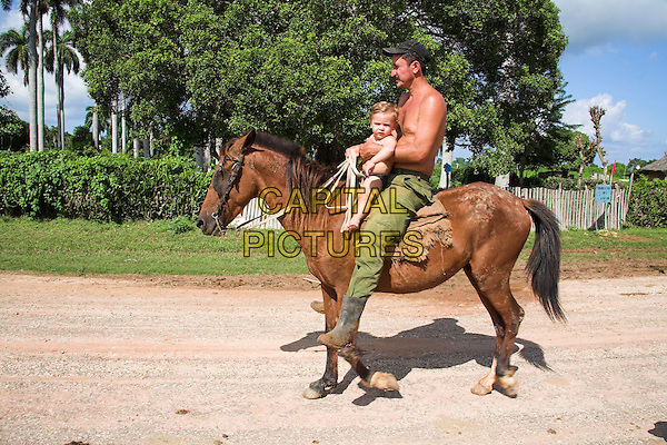 Father and son riding on a horse, Chorro de Maita, near Guardalavaca, Holguin Province, Cuba