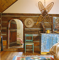 Antique snow shoes and a Navajo rug decorate the rustic interior of this restored log cabin