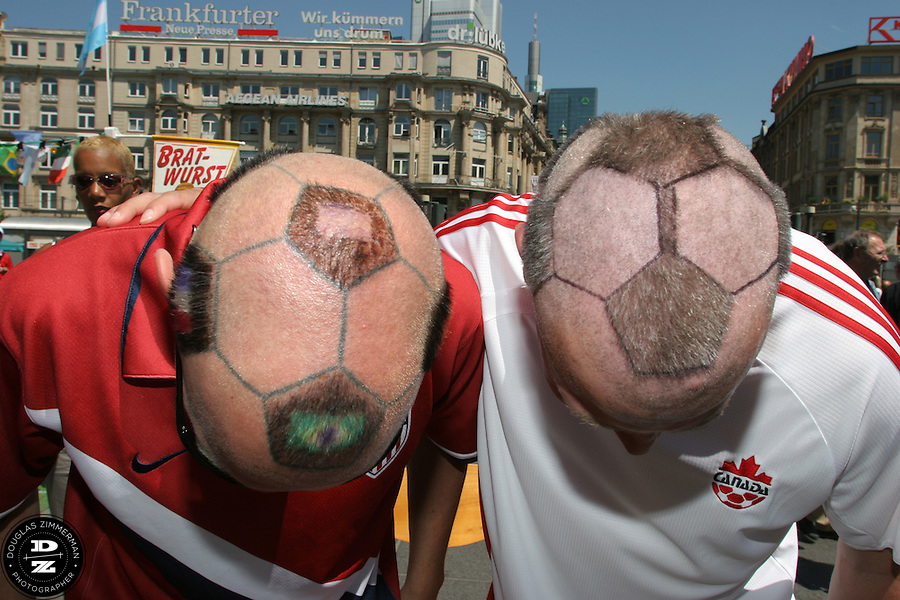 USA National Soccer Team fan Zack Phillips, also known as Mr. Soccerhead, of San Francisco, Calif. and Canadian soccer fan Yuri Smieska of Hamilton, Ontario show off their soccer ball haircuts.  Phillips had cut the hair of Smieska into the design of a soccer ball outside the Frankfurt Main Train Station in Frankfurt-am-Main, Germany on Tuesday, June 13, 2006.  The hair cut attracted the attention of many curious travelers. For the previous ten years, Zack Phillips has cut the hair on his head in the design of a soccerball and has even tattoed the design to make it easier to cut. At the 2002 World Cup in Korea Zack cut the hair of Yuri Smieska and Yuri asked Zack if he could do it again this World Cup. They met up outside the train station before Yuri went  to the Korea-Togo FIFA World Cup first round match in Frankfurt-am-Main with some fellow Canadian friends.