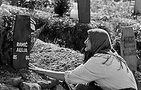 A Bosnian woman cries as she touches her son's grave in Sarajevo's Lion's cemetery on August 23, 1994.