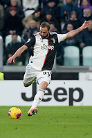 6th January 2020; Allianz Stadium, Turin, Italy; Serie A Football, Juventus versus Cagliari; Gonzalo Higuain of Juventus shoots and scores the goal for 3-0 for Juvntus in the 81st minute - Editorial Use