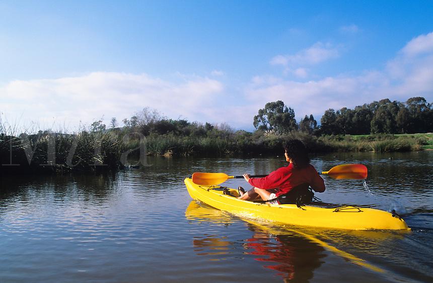 Woman paddling a kayak on a lake.