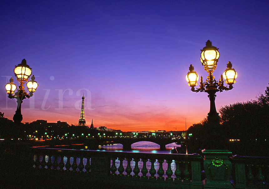 Streetlights glow at twilight on a bridge spanning the River Seine. Paris, France.
